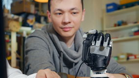 Ingenieur an modernem fangen oben Büro an, mit dem innovativen bionischen Roboterarm zu arbeiten Transportwagenkamerabewegung stock footage