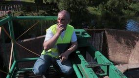 Ingenieur op de walkie-talkie en het controleren van de sluisdeur stock video