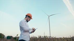 Ingenieur in oranje bouwvakker bij windmolenelektrische centrale met tablet in hand op hemelachtergrond Langzame Motie De turbine stock videobeelden
