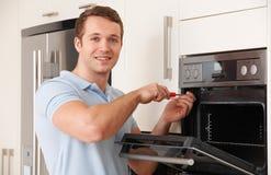 Ingenieur Reapiring Domestic Oven In Kitchen royalty-vrije stock afbeelding