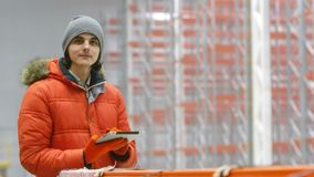 Ingenieur schaut die Tablette und auf den Seiten innerhalb eines neuen modernen Lagers