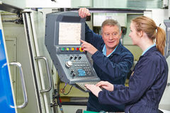 Ingenieur Showing Apprentice How aan Gebruik Geautomatiseerde Scherpe Mach stock fotografie