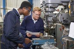 Ingenieur Showing Apprentice How aan Gebruiksboor in Fabriek stock afbeelding