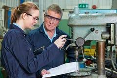 Ingenieur Showing Apprentice How aan Gebruiksboor in Fabriek stock fotografie