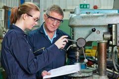 Ingenieur Showing Female Apprentice hoe te om Boor in Fabriek te gebruiken stock afbeeldingen
