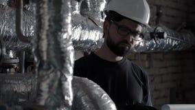 Ingenieur of technicus het werk in ketelruim dichtbij pijpen, neemt nota's stock footage