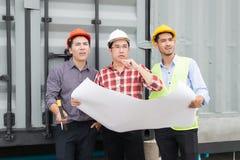 Ingenieur und Bau team tragenden Schutzhelm und Plan an Hand sie sind Überprüfungsmaterial und -Bauprozess lizenzfreies stockfoto