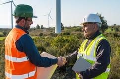 Ingenieur und Geologe beraten sich nah an Windkraftanlagen in der Landschaft lizenzfreie stockbilder