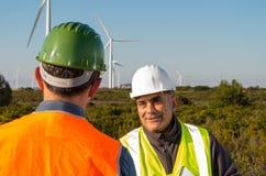 Ingenieur und Geologe beraten sich nah an Windkraftanlagen in der Landschaft stockbild