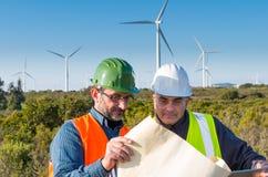 Ingenieur und Geologe beraten sich nah an Windkraftanlagen in der Landschaft lizenzfreie stockfotos