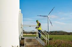 Ingenieur und Geologe beraten sich nah an Windkraftanlagen in der Landschaft lizenzfreie stockfotografie