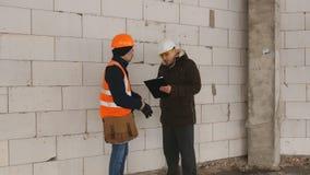 Ingenieur und Vorarbeiter an der Baustelle im Winter, Dokumentation zur Baustelle besprechen stock footage