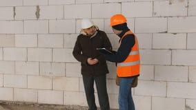 Ingenieur und Vorarbeiter an der Baustelle im Winter, Dokumentation zur Baustelle besprechen stock video