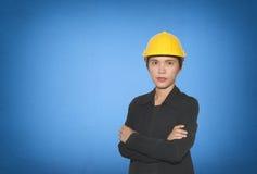 Ingenieur van Aziatische vrouwen in dwars het wapen van ` s op blauwe concrete muur royalty-vrije stock afbeelding