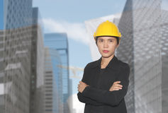 Ingenieur van Aziatische vrouwen in dwars het wapen van ` s op wolkenkrabbers backgr stock afbeelding