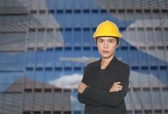 Ingenieur van Aziatische vrouwen in dwars het wapen van ` s op wolkenkrabbers backgr royalty-vrije stock foto