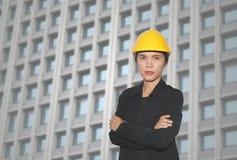 Ingenieur van Aziatische vrouwen in dwars het wapen van ` s op wolkenkrabbers backgr stock fotografie
