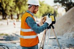 Ingenieur in weerspiegelend vest en witte helm die geodetic equi gebruiken royalty-vrije stock foto's