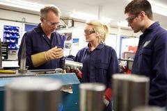 Ingenieur Working With Apprentices op Fabrieksvloer Stock Fotografie