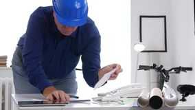 Ingenieur Working im Büro berechnen unter Verwendung der Rechenmaschine und schreiben auf ein Papier stock footage