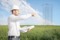 Ingenieurarchitekt mit Zeichnungen im weißen Sturzhelm zeigt Baustelle des zukünftigen Immobiliengegenstandes des Wohngebäudes lizenzfreie stockbilder