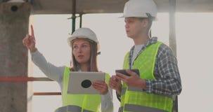 Ingenieurdesigner stehen auf dem Dach des Gebäudes im Bau und besprechen den Plan und den Fortschritt von stock footage