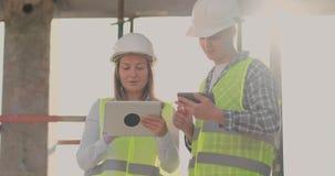 Ingenieurdesigner stehen auf dem Dach des Gebäudes im Bau und besprechen den Plan und den Fortschritt von stock video