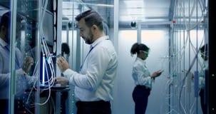 Ingenieure arbeiten mit Kabeln im Serverraum stock video