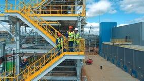 Ingenieure, die ein neues Projekt besprechen Großer Industriehintergrund stock footage