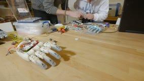 Ingenieure, die am High-Techen innovativen bionischen Arm an der Werkstatt arbeiten stock video