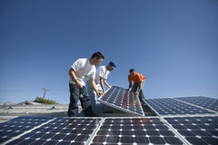 Ingenieure, die Sonnenkollektor gegen Himmel in Position bringen stockbilder