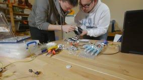 Ingenieure im Labor besprechen den bionischen Roboterarm, der auf Drucker 3D hergestellt wird stock footage