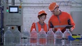 Ingenieure Kerl und Mädchen in Sturzhelm und Funktionskleidung nahe Fördererlinie für das Abfüllen des Mineralwassers in den Plas stock video footage