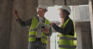 Ingenieure oder Architekten haben eine Diskussion an der Baustelle, die durch den Plan des Baus schaut contre jour stock footage