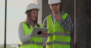 Ingenieure oder Architekten haben eine Diskussion an der Baustelle, die durch den Plan des Baus schaut contre jour stock video