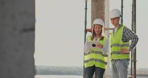 Ingenieure oder Architekten haben eine Diskussion an der Baustelle, die durch den Plan des Baus schaut contre jour stock video footage