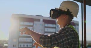 Ingenieurerbauer auf dem Dach des Gebäudes bei Sonnenuntergang steht in vr Gläsern und bewegt seine Hände unter Verwendung der Sc stock video footage
