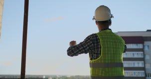 Ingenieurerbauer auf dem Dach des Gebäudes auf Sonnenuntergangständen in VR-Gläsern und -bewegungen seine Hände unter Verwendung  stock video footage