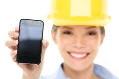 Ingenieurfrau, die intelligentes Telefon zeigt stockfotos