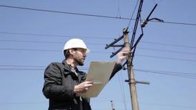 Ingenieurkontrollelektrische Systeme sprechen Funksprechgerät, den Inspektor, der Pläne hält, planen stock footage