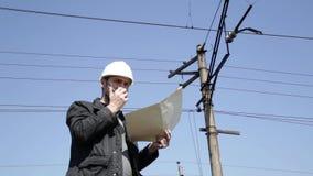 Ingenieurkontrollelektrische Systeme sprechen Funksprechgerät, den Inspektor, der Pläne hält, planen stock video