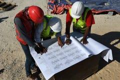 Ingenieurs in de bouwwerf met Blauwdrukken stock afbeelding