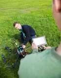 Ingenieurs die aan UAV Helikopter bij Park werken stock afbeeldingen