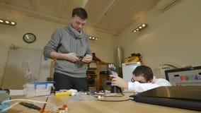 Ingenieurs die bij hi-tech innovatief bionisch wapen op workshop werken stock videobeelden