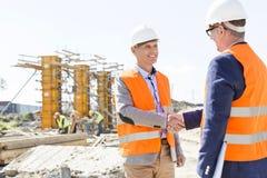Ingenieurs die handen schudden bij bouwwerf tegen duidelijke hemel Royalty-vrije Stock Afbeeldingen