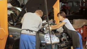 Ingenieurs die met motor van een auto werken stock video