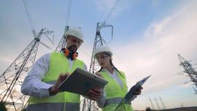 Ingenieurs die met tablet dichtbij machtshulpkantoor werken, elektrohulpkantoor, elektrisch hulpkantoor stock video