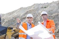 Ingenieurs die over blauwdruk bij bouwwerf bespreken Royalty-vrije Stock Afbeelding