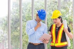 Ingenieurs die vergaderzaal met een tablet werken Twee arbeiders letten bouw op plan op het kantoor Elektricienstimmerman of royalty-vrije stock afbeeldingen