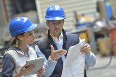 Ingenieurs in het metallurgische fabriek bespreken royalty-vrije stock afbeelding